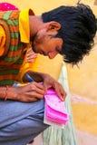 Homme local écrivant un reçu en Amber Fort près de Jaipur, Ràjasthàn Photographie stock libre de droits