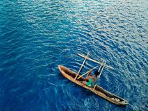 homme local barbotant avec son canoë de tangon au rivage avec un porcelet au milieu de la mer bleue profonde tropicale photo stock