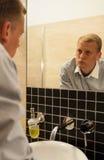 Homme luttant avec la dépendance dans la salle de bains Image libre de droits