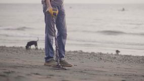 Homme méconnaissable avec le sable électronique de balayage de détecteur de métaux sur la plage avec le détecteur de métaux trouv clips vidéos