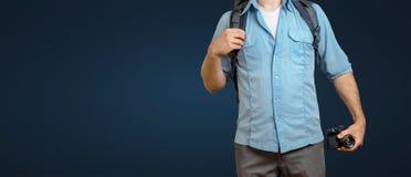 Homme méconnaissable de Blogger de voyageur avec l'appareil-photo de sac à dos et de film sur le fond bleu Hausse du concept de v photos libres de droits