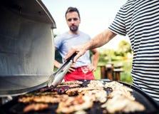 Homme méconnaissable faisant cuire des fruits de mer sur un gril de barbecue dans l'arrière-cour Fin vers le haut photographie stock
