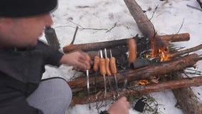 Homme méconnaissable faisant frire les saucisses juteuses délicieuses en parc neigeux clips vidéos