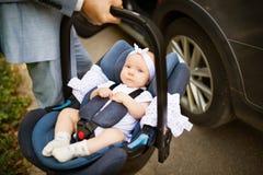 Homme méconnaissable portant son bébé dans un siège de voiture Images libres de droits