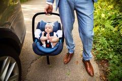 Homme méconnaissable portant son bébé dans un siège de voiture Photos libres de droits