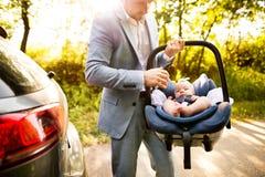 Homme méconnaissable portant son bébé dans un siège de voiture Photos stock