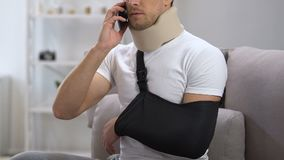 Homme mécontent dans le collier cervical de mousse et le téléphone parlant de bride de bras, problème clips vidéos