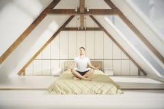 Homme méditant dans la chambre à coucher de grenier Photos libres de droits