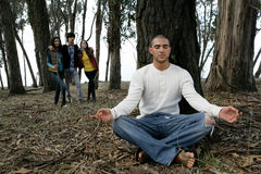 Homme méditant dans la forêt Photos stock