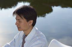 Homme méditant par l'étang dans le matin Photo stock