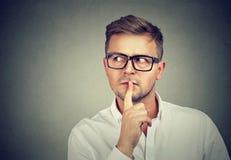 Homme méfiant tenant le doigt sur des lèvres images stock