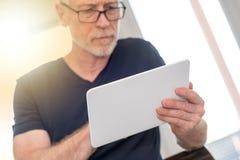 Homme mûr à l'aide du comprimé numérique, effet de la lumière Images stock
