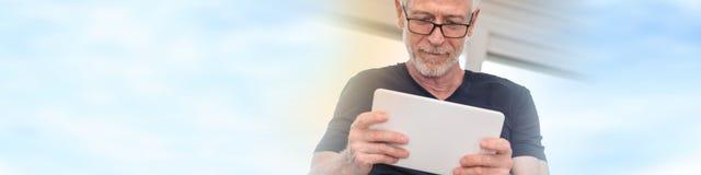 Homme mûr à l'aide du comprimé numérique, effet de la lumière Image libre de droits