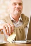 Homme mûr aîné - achats à la maison avec par la carte de crédit Photo stock