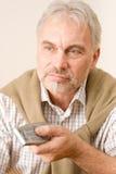 Homme mûr aîné avec à télécommande Photo stock
