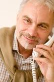 Homme mûr aîné heureux au téléphone Photos stock