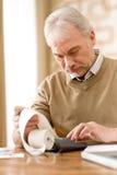 Homme mûr aîné - Home Office avec la calculatrice Photographie stock