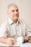 Homme mûr aîné - Home Office, calculatrice de bande Photo stock