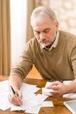 Homme mûr aîné - Home Office, calculatrice de bande Images libres de droits