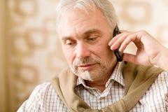 Homme mûr aîné pensif avec le téléphone portable Image stock