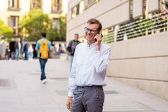 Homme mûr attirant heureux à son téléphone intelligent tout en marchant dans le sourire de rue photo stock