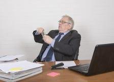 Homme mûr au travail, buvant d'un flacon Image stock