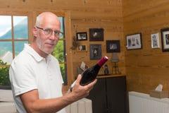 Homme mûr avec la bouteille de vin rouge, à la maison Photos stock
