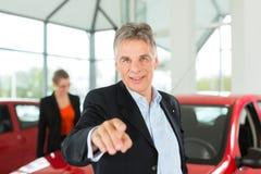 Homme mûr avec le femme et l'automobile au concessionnaire automobile Image stock