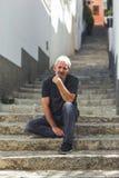 Homme mûr avec les cheveux blancs se reposant sur des étapes urbaines Image libre de droits
