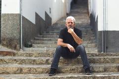 Homme mûr avec les cheveux blancs se reposant sur des étapes urbaines Images libres de droits