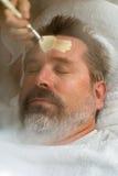 Homme mûr ayant le massage facial photo stock
