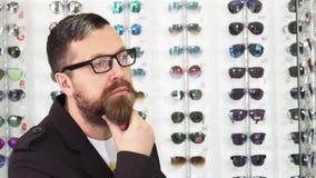 Homme mûr barbu frottant sa barbe choisissant pensivement de nouveaux verres banque de vidéos