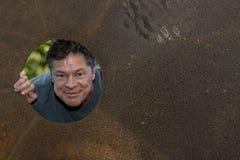 Homme mûr bel dans le trou de plat de fer, regardant loin, grimaces, heureux, satisfaites image stock