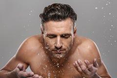 Homme mûr bel se lavant le visage photographie stock