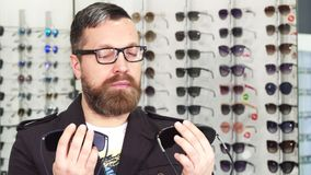 Homme mûr choisissant entre deux paires de lunettes de soleil au magasin photographie stock libre de droits