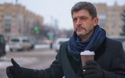 Homme mûr dans un manteau et une écharpe tenant le café essayant de prendre un taxi Photographie stock libre de droits