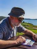 Homme mûr dans un touriste d'habillement d'été s'asseyant par les informations de lecture de lac sur l'endroit de l'Ecosse photographie stock libre de droits