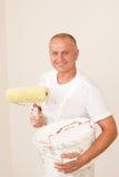 Homme mûr de décoration à la maison avec le rouleau de peinture Images stock