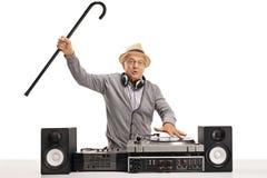 Homme mûr enthousiaste jouant la musique sur une plaque tournante photo stock