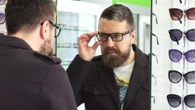 Homme mûr essayant sur de nouveaux verres dans l'avant si le miroir au magasin banque de vidéos