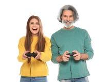 Homme mûr et jeune femme jouant des jeux vidéo avec des contrôleurs sur le blanc photo stock