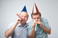 Homme mûr et son jeune fils célébrant le joyeux anniversaire utilisant les chapeaux drôles image libre de droits
