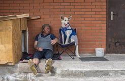 Homme mûr habillé sale s'asseyant près du mur de briques image libre de droits