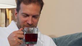 Homme mûr heureux appréciant sentant le thé chaud délicieux, se reposant à la maison banque de vidéos