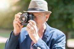 Homme mûr prenant des photos, effet de la lumière Photo stock