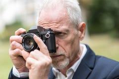 Homme mûr prenant des photos, effet de la lumière Image libre de droits