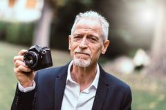 Homme mûr prenant des photos, effet de la lumière Images libres de droits