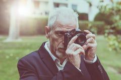 Homme mûr prenant des photos, effet de la lumière Images stock