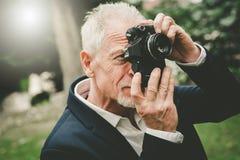 Homme mûr prenant des photos, effet de la lumière Photos libres de droits