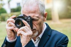 Homme mûr prenant des photos, effet de la lumière Photographie stock libre de droits